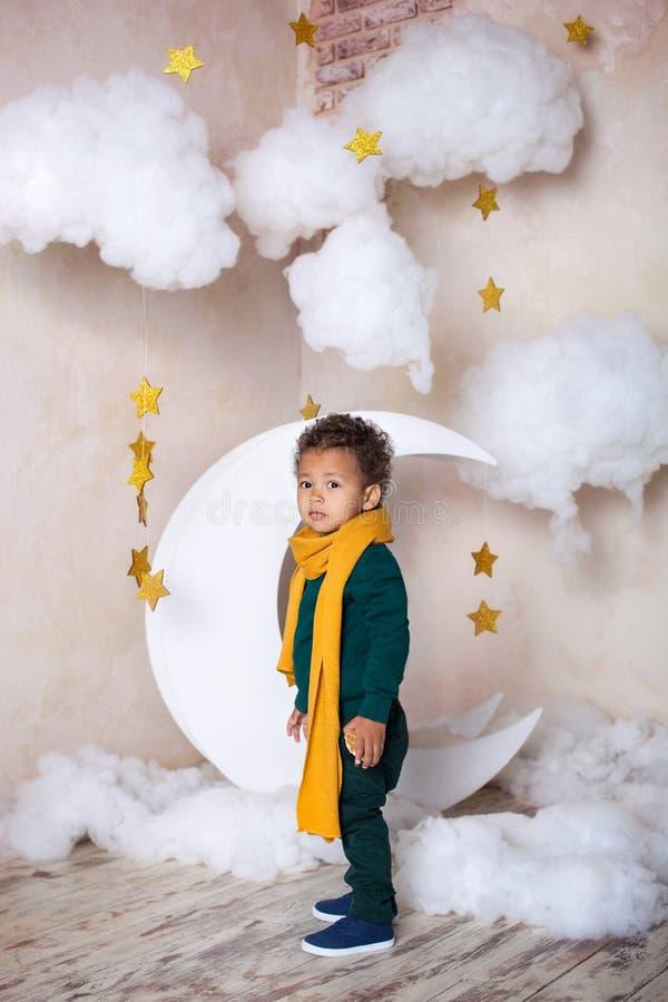 Черный мальчик стоит около месяца, nluna, среди звезд Ребенок в игре, в фантазии Приключения маленького принца Afric стоковые фото