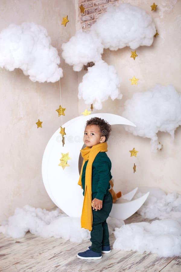 Черный мальчик стоит около месяца, nluna, среди звезд Ребенок в игре, в фантазии Приключения маленького принца Afric стоковое фото rf