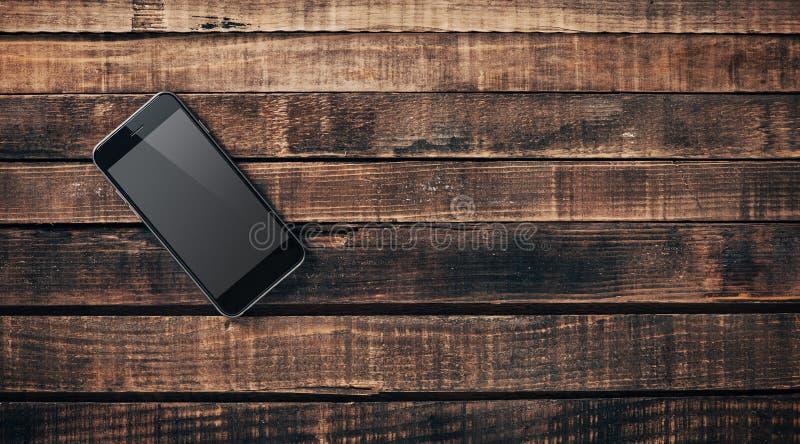 Черный мобильный телефон на деревянном столе стоковые фотографии rf