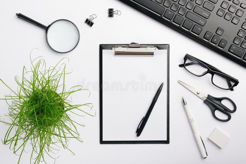 Черный модель-макет доски сзажимом для бумаги место для работы стола с черной клавиатурой, стеклами, ручками, ластиком и другими  стоковое изображение rf