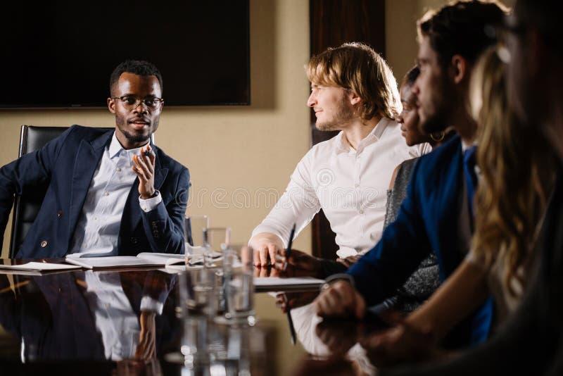 Черный мужской босс говоря к команде дела в конференц-зале стоковое изображение rf
