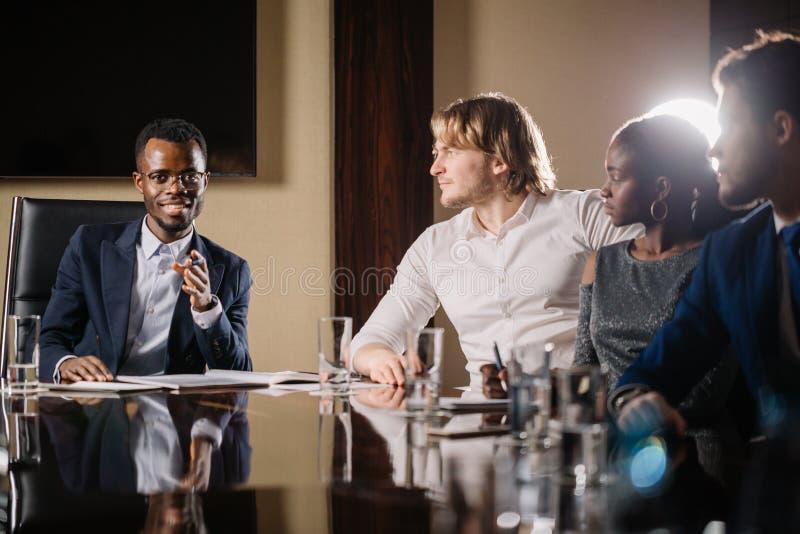 Черный мужской босс говоря к команде дела в конференц-зале стоковые фото