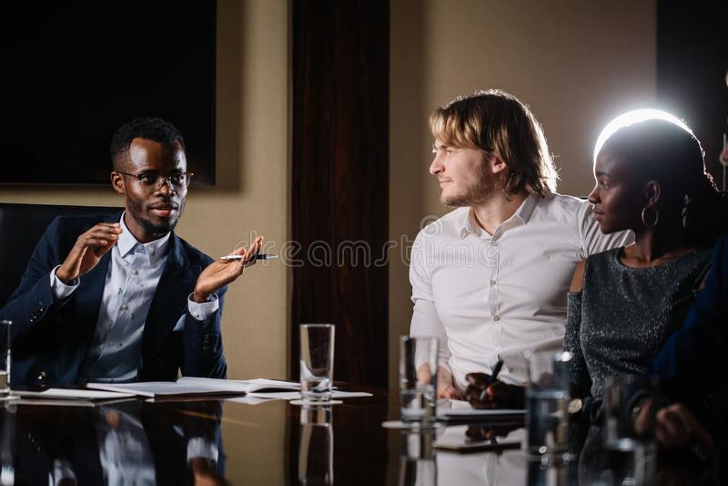 Черный мужской босс говоря к команде дела в конференц-зале стоковая фотография