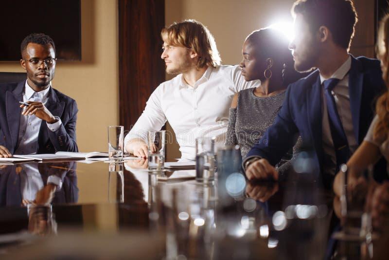 Черный мужской босс говоря к команде дела в конференц-зале стоковое изображение