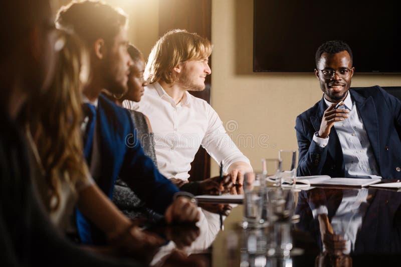 Черный мужской босс говоря к команде дела в конференц-зале стоковые фотографии rf