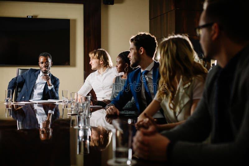 Черный мужской босс говоря к команде дела в конференц-зале стоковые изображения rf