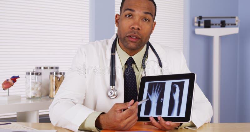 Черный доктор рассматривая рентгеновский снимок запястья руки стоковое фото