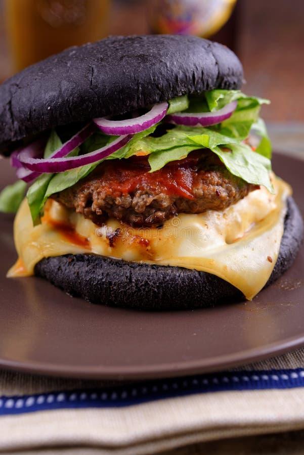 Черный пакостный бургер стоковое изображение