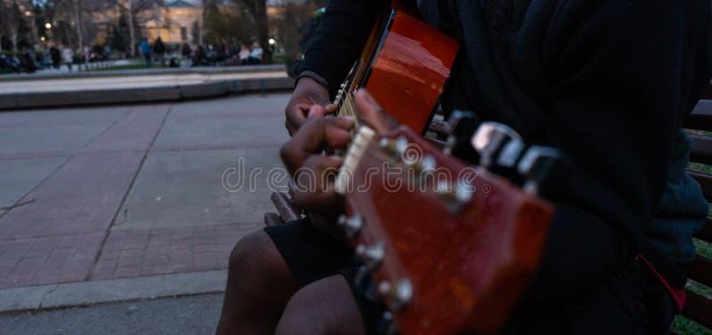 Черный парень играя гитару и поя счастливое усаживание в стенде парка стоковая фотография rf