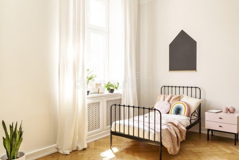 Черный плакат над кроватью ребенк в белом интерьере спальни с заводами и задрапировывает на окне Реальное фото стоковое фото rf