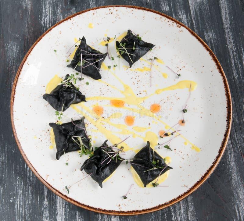 Черный равиоли с морепродуктами На взгляде сверху плиты На деревянной черной предпосылке стоковое фото rf