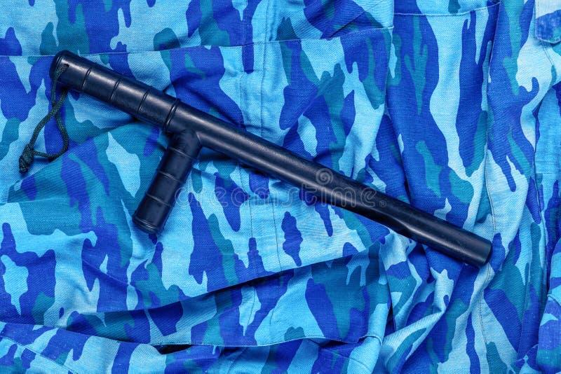 Черный резиновый жезл на голубом городском русском камуфлировании полиции по охране общественного порядка плоском кладет стоковая фотография