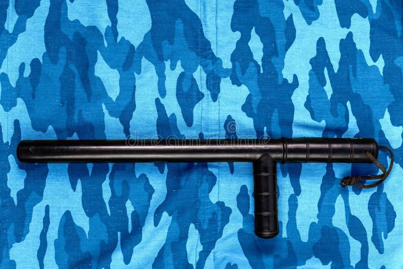 Черный резиновый жезл на голубом городском русском камуфлировании полиции по охране общественного порядка плоском кладет стоковое фото
