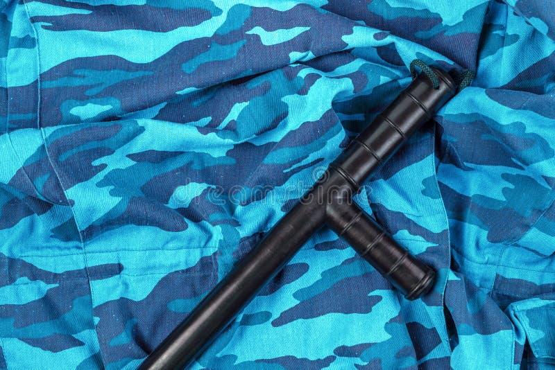 Черный резиновый жезл на голубом городском русском камуфлировании полиции по охране общественного порядка плоском кладет стоковые фотографии rf