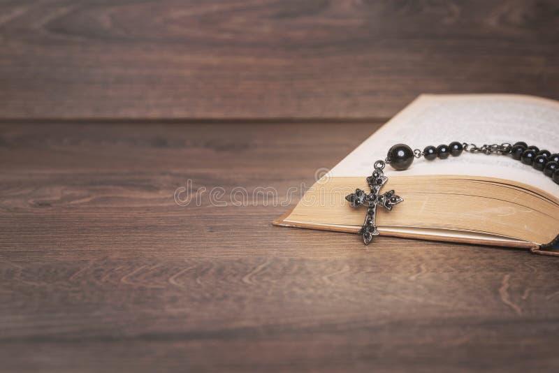 Черный розарий на библии на деревянном столе стоковые изображения