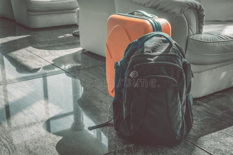Черный рюкзак и оранжевая стойка чемодана в зале на приеме Багаж для перемещения стоковая фотография