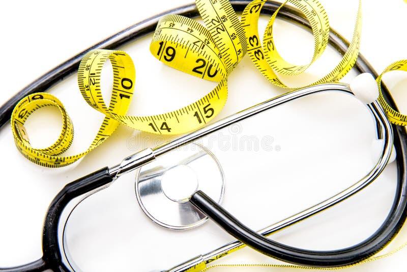Черный стетоскоп & желтая лента диеты на белизне стоковое изображение rf