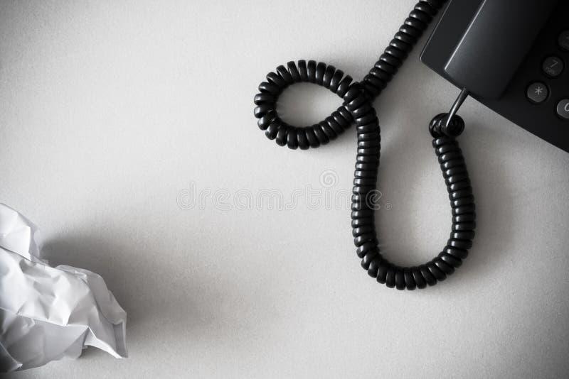 Черный телефон и белизна наземной линии скомкали бумагу на текстурированной поверхности гранита стоковые фото