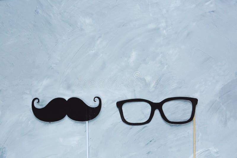Черный усик, стекла от бумаги на ручке на серой предпосылке grunge стоковое фото rf