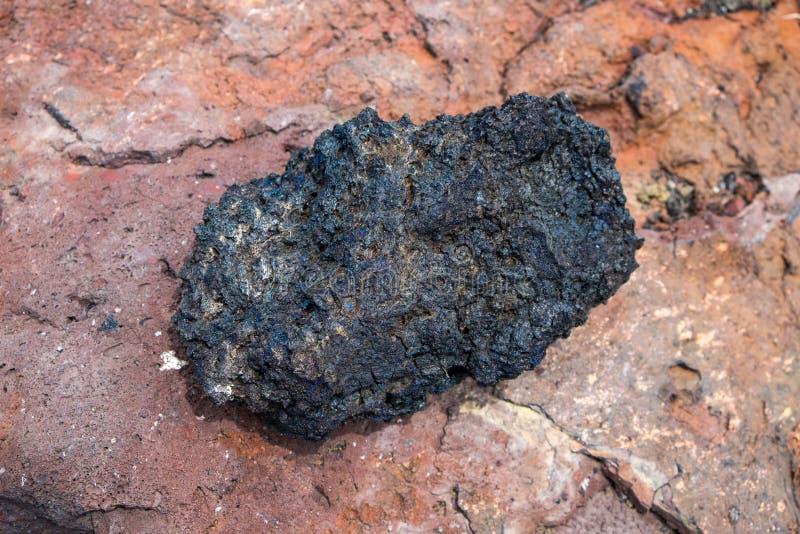 Черный утес лавы от вулкана на предпосылке пемзы стоковые фото