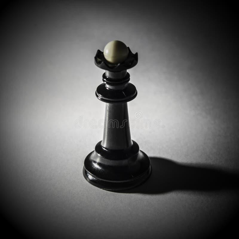 Черный ферзь шахмат стоит на белой предпосылке, плотной тени, радиальном градиенте стоковое фото rf