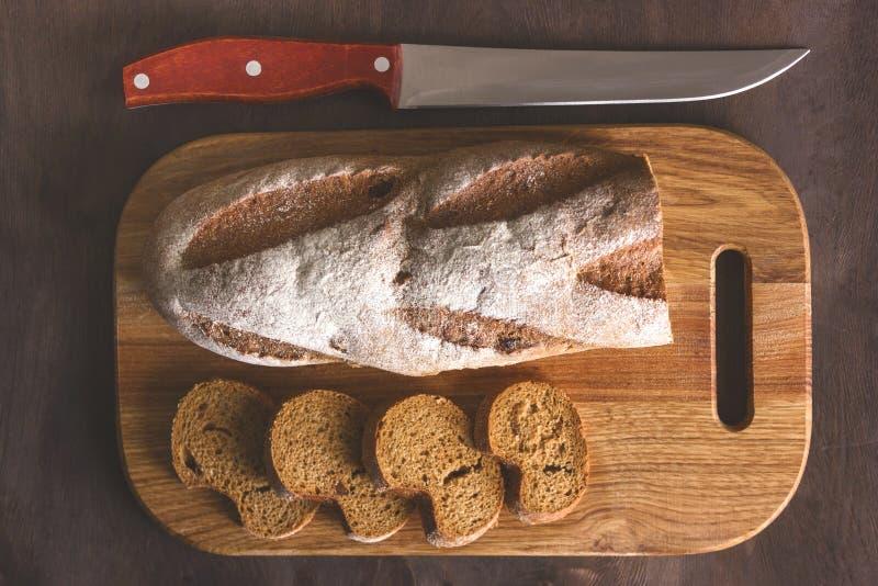 Черный хлеб на разделочной доске с ножом стоковая фотография