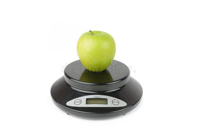 Черный цифровой масштаб, утяжеляет зеленое яблоко стоковое изображение rf