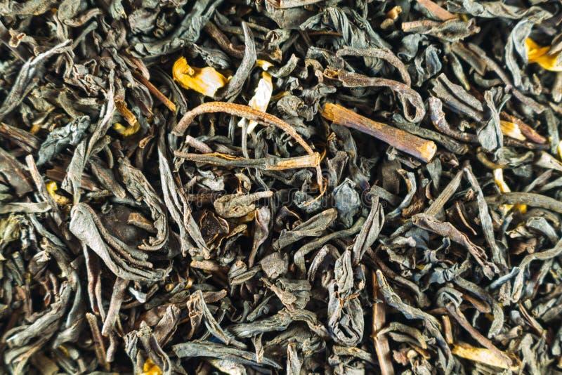 Черный чай, сухие листья с цветками для всех фото обои стоковое изображение rf