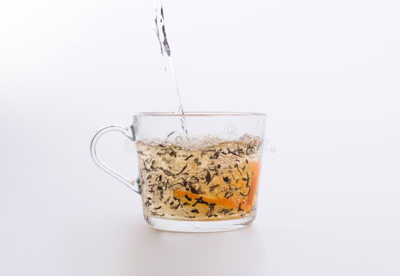 Черный чай с оранжевый лить в стеклянную изолированную чашку стоковые изображения rf