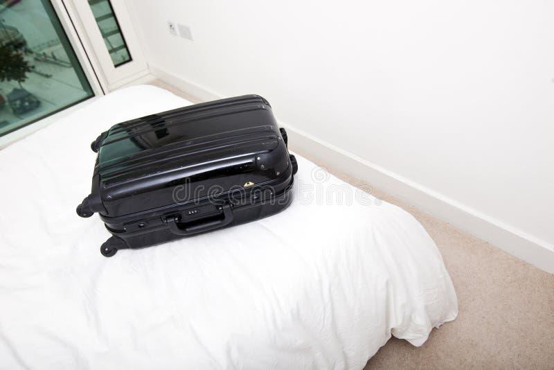 Черный чемодан на кровати стоковое изображение