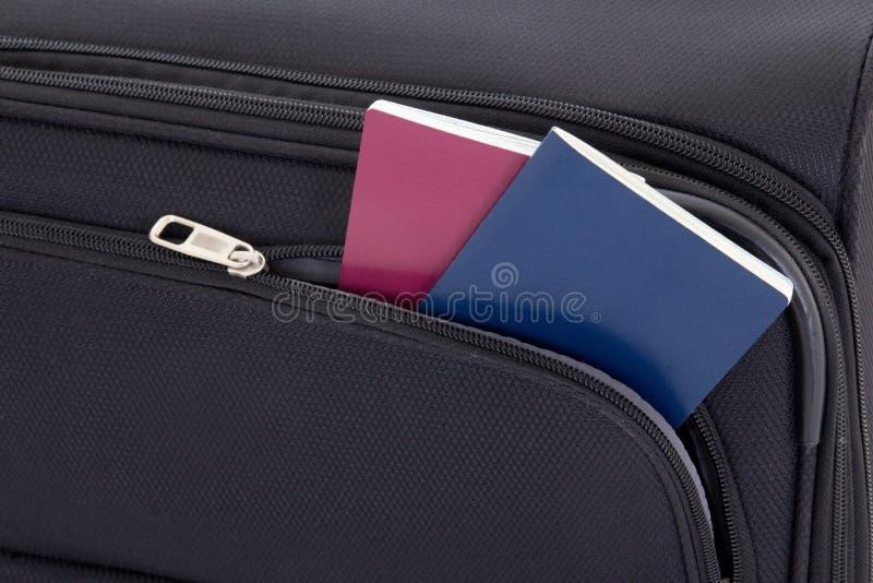 Черный чемодан перемещения и 2 пасспорта стоковые изображения rf