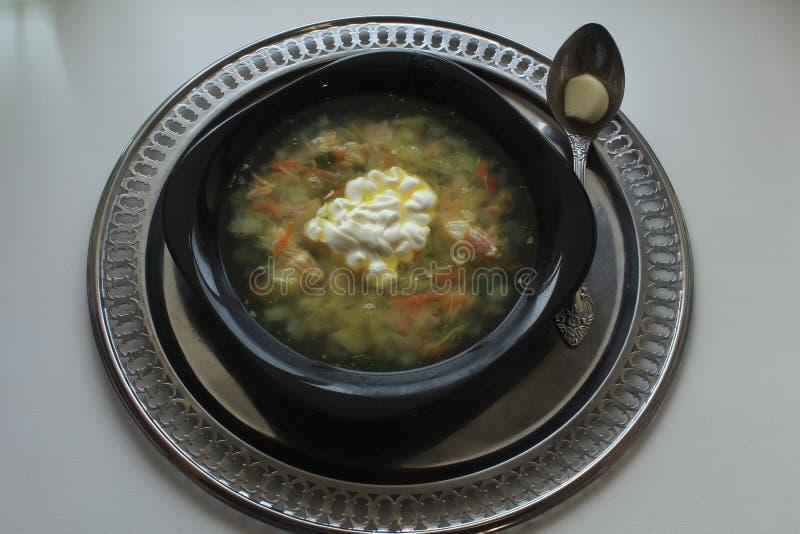 Черный шар супа и ложки на подносе стоковое изображение rf