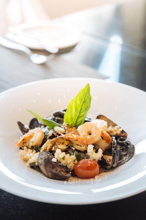 Черный fettuccine с креветкой, кальмаром и clam Макаронные изделия чернил кальмара морепродуктов стоковое фото