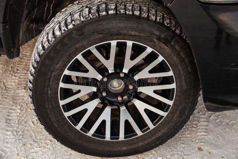 Черный Ram доджа с двигателем 5 7 литров взгляда переднего колеса на автостоянке с предпосылкой снега стоковые изображения rf