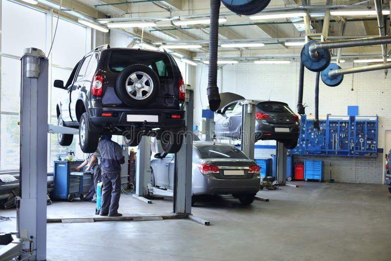 3 черных автомобиля стоят в малой станции обслуживания и 2 людях стоковые фотографии rf