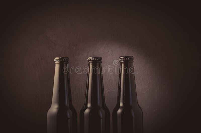 3 черных бутылки пива на темной предпосылке/3 черных бутылках пива на темной предпосылке со светом Селективный фокус стоковая фотография