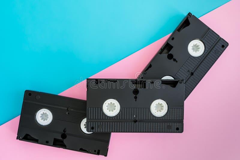 3 черных магнитной ленты для видеозаписи VHS лежа раскосно на яркой розовой и голубой предпосылке стоковая фотография rf