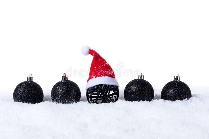 5 черных шариков рождества при снег и шляпа Санты изолированные на белой предпосылке стоковые изображения rf