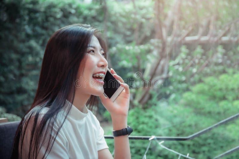 Чернь красивой девушки азиата держа и иметь мобильный телефон эмоции счастливый смотря стоковое фото rf