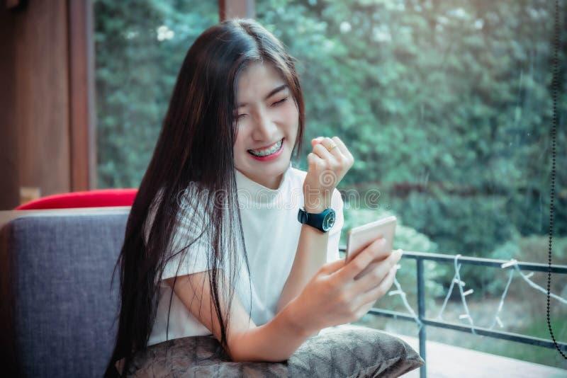 Чернь красивой девушки азиата держа и иметь мобильный телефон эмоции счастливый смотря стоковое изображение rf