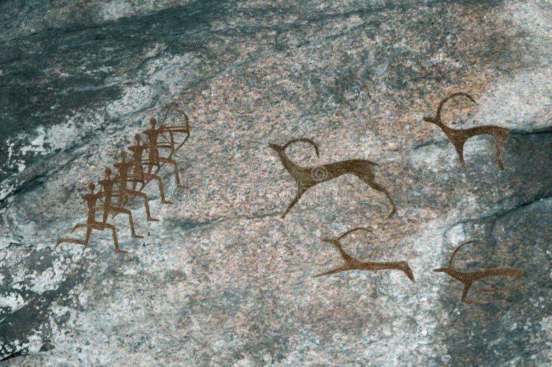 Чертежи в пещере Доисторические животные охоты людей стоковое фото