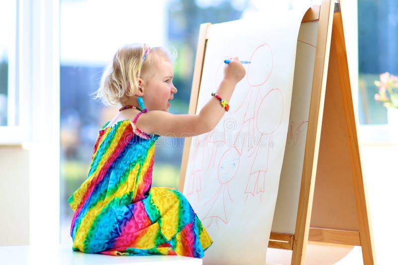 Чертеж девушки Preschooler с карандашами на бумаге стоковое фото rf