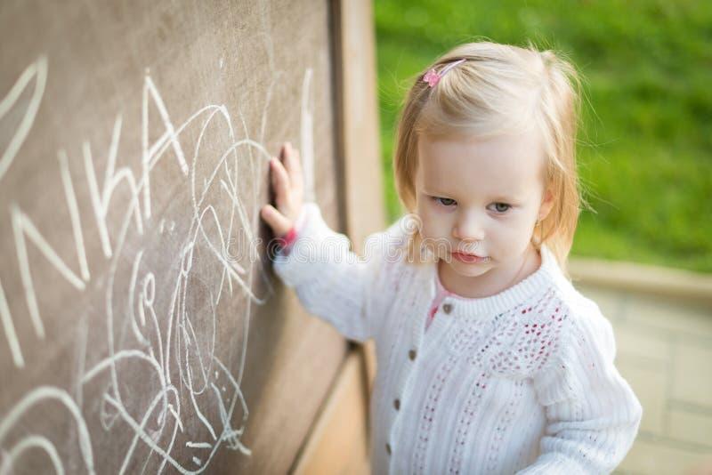 Чертеж маленькой девочки на классн классном Девушка малыша имея потеху outdoors, держащ мел и рисовать стоковое фото rf