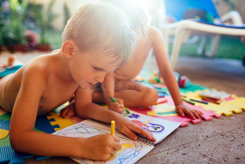 Чертеж мальчика и девушки с crayons стоковое изображение