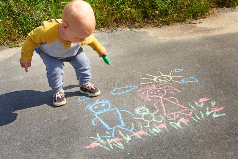 Чертеж мальчика с мелом на асфальте, счастливой семьей: outdoors папы, мамы и младенца стоковые фотографии rf