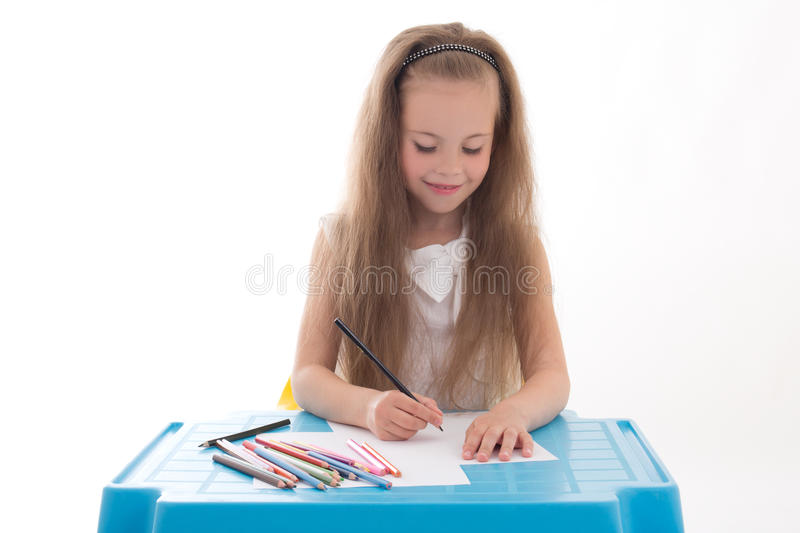 Чертеж маленькой девочки используя карандаши цвета изолированные на белизне стоковые изображения
