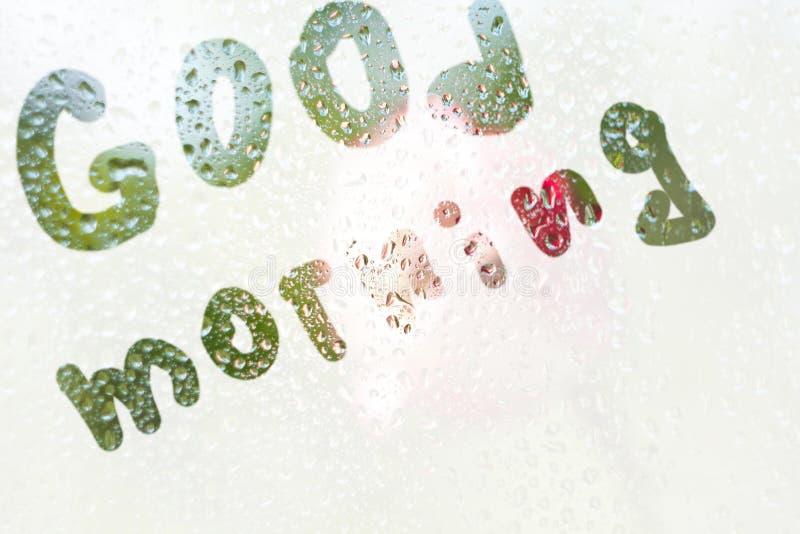 Чертеж пальца формы нашивок доброго утра слова на просвечивающем misted стекле дождевые капли весеннего дождя дальше стоковое изображение