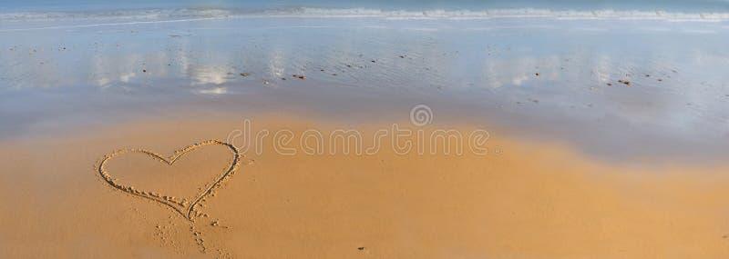 Чертеж сердца на песке перед морем стоковые фото