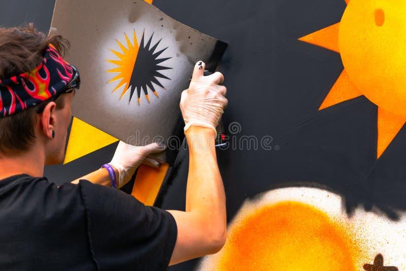 Чертеж с брызгами - картина молодого человека художника граффити с консервными банками цвета аэрозоля на стене стоковое фото rf