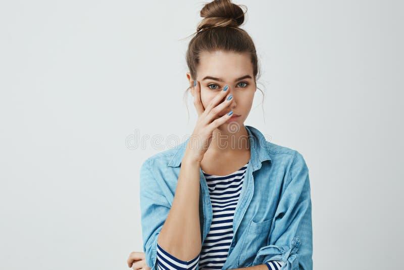 Черт возьми вы нося Портрет девушки которая чувствует смущенной, покрывающ сторону при ладонь, смотря что-то стоковая фотография